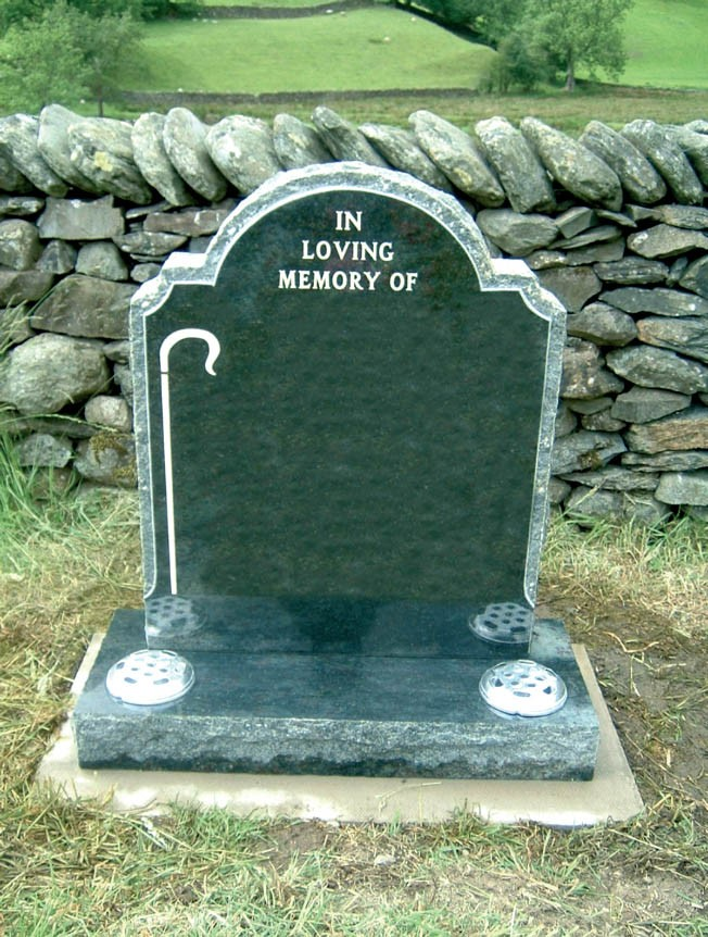 PJ36 - This hand carved dark grey granite memorial with a distinctive shape complimented here with the shepherds crook.  Bespoke Headstones, Lawn Memorials